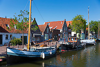 Sailing boats, sailboats, moored along canal waterway in front of traditional houses at  Edam in The Netherlands