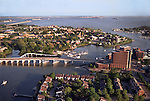 Hampton, Virginia on the James River May 2000. Norfolk &amp; Virginia Beach are in the distance across Hampton Roads (James River) exit to the Chesapeake Bay &amp; Atlantic Ocean. An outbound ship is crossing the channel at the I-64  Bridge Tunnel at center. Hampton University is at center between the foreground river and the larger body of water in the distance..