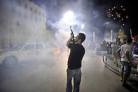 A man smokes as he fires a gun into the air celebrating in Martyrs' Square in Tripoli. After a six month revolution, rebel forces finally managed to break into Tripoli and have taken control of Bab al-Aziziyah, Col Gaddafi's compound and residence. Few remain that are loyal to Gaddafi in the city; it is seeming that the 42 year regime has come to an end. Gaddafi is currently on the run.