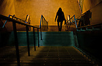 A lone silhouetted woman walking down stairs into a train station.