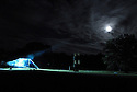 K.C. testing the Night Stage lights under a full moon. 2006. ..Image from the book project Welcome Home: Building the Michigan Womyn's Music Festival, self-published First-Edition 2009...Photo by Angela Jimenez.copyright 2009 Angela Jimenez Photography