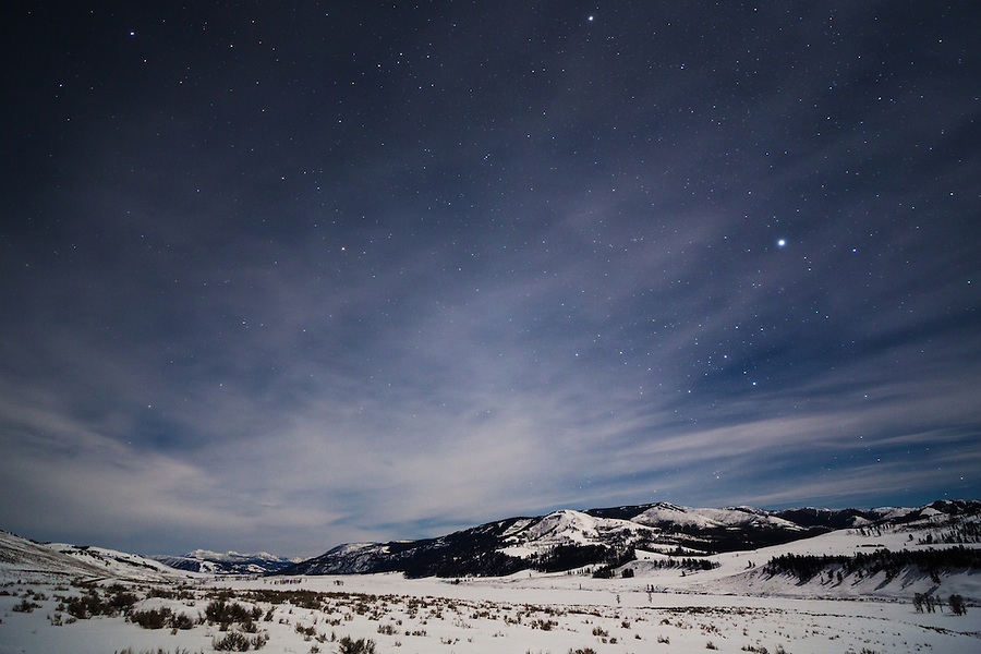 Stars and light clouds shine above the Lamar Valley in Yellowstone National Park, Wyoming at night.