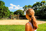 Girl seen from back looking at empty baseball field in summer, Merrick, New York, 2008.