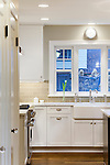 Crisp white cabinetry and white marble counters set against dark wood floors