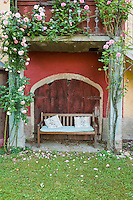 A simple wooden bench sitting in the garden under a balcony covered in pale pink climbing roses makes for a romantic scene