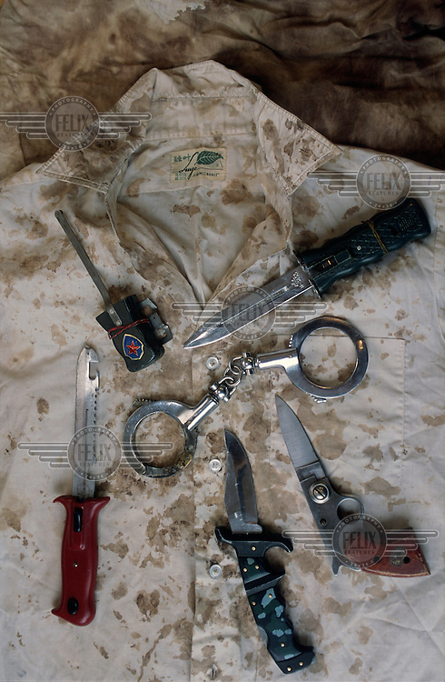 Knives, saws and handcuffs; examples of instruments of torture used in Chinese prisons on Tibetan people, laid out on the blood stained shirt of a monk..
