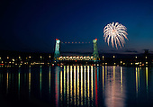 4th of July fireworks above the Douglass Houghton bridge between Houghton and Hancock in Michigan's Upper Peninsula. Portage Canal in foreground.