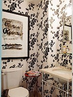 A black and white floral pattern wallpaper dominates a small bathroom