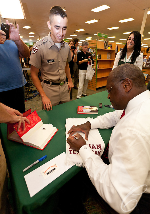 """Presidential candidate Herman Cain signs a """"12th Man"""" Towel for Texas A&M Corps of Cadets freshman David Garcia at a College Station, Texas book signing. College Station is the home of Texas A&M University and the alma mater Cain's Republican rival Rick Perry."""