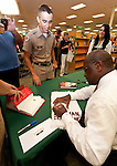 "Presidential candidate Herman Cain signs a ""12th Man"" Towel for Texas A&M Corps of Cadets freshman David Garcia at a College Station, Texas book signing. College Station is the home of Texas A&M University and the alma mater Cain's Republican rival Rick Perry."