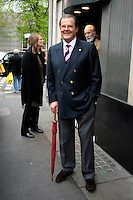 MAUD ADAMS, SIR ROGER MOORE & CHRISTOPHER LEE (background).Having a Bond reunion lunch at The Ivy Club this afternoon, London, England..April 26th, 2010.full length blue suit jacket grey gray trousers umbrella .CAP/DYL.©Dylan/Capital Pictures.