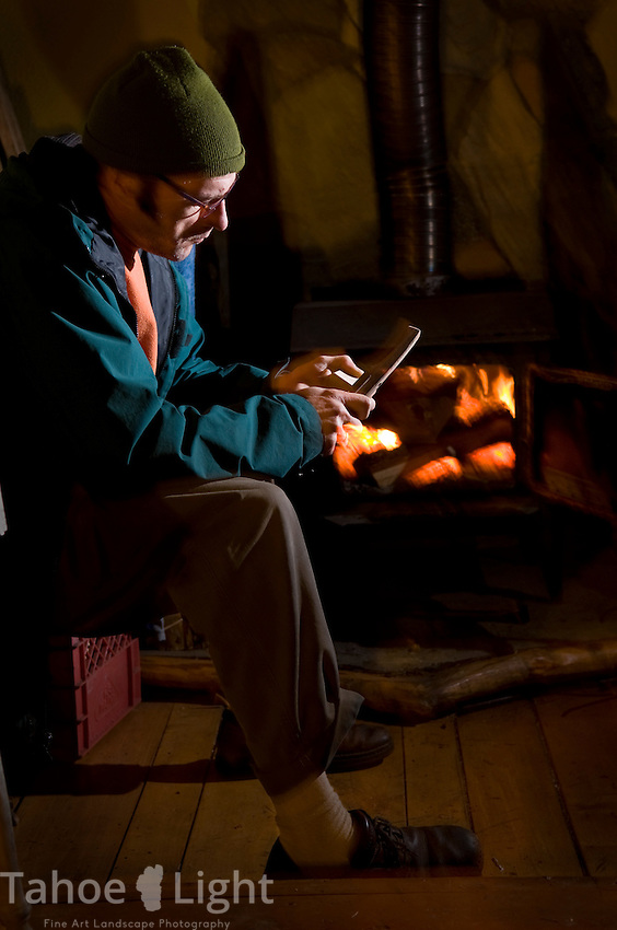 Dan Cearley working wood by his stove in his cabin in robert's creek.