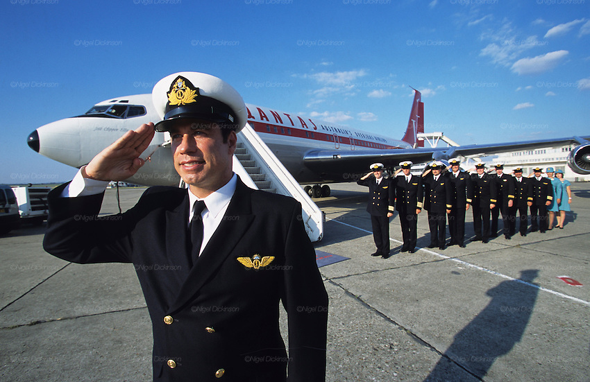 "John Travolta, Captain and pilot, of his own jumbo jet, salutes, with his plane and crew behind...John Travolta is pilot of his very own jumbo jet, a 1964 Boeing 707-100 series. In 2003, John Travolta flew his jumbo jet around the world, in partnership with Quantas, to rekindle confidence in commercial aviation, and to remind us that elegance and style are a part of flying. The crew are dressed in tailor made authentic uniforms from the Quantas museum. The men's uniforms are styled on British Naval uniforms and the ladies' designed by Chanel. His jumbo jet sports a personalised number plate N707JT which speaks for itself. The aircraft is named ""Jett Clipper Ella"" dedicated to his son and daughter. This jumbo together with his other aircraft are housed in purpose built hangars at his home in Florida, USA"
