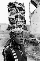 Angola. Province of Bié. Kuito. The town was heavily destroyed in 1993-1994 and 1998-1999 due to the intense civil war between the Government and Unita. A woman carries on her head a plastic shopping bag with the image of the statue of liberty. © 2000 Didier Ruef