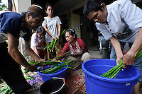 A disabled woman preparing water hyacinth, Makassar, Sulawesi, Indonesia.  The hyacinth is then used to produce material for sandals.
