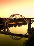 The arched steel Edmund Pettus Bridge is reflected at sunset in the still waters of the Alabama River.  The bridge played a major role in the American Civil Rights Movement in 1965.