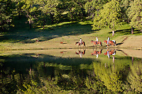 Ranch hand's on horseback riding beside a calm pond