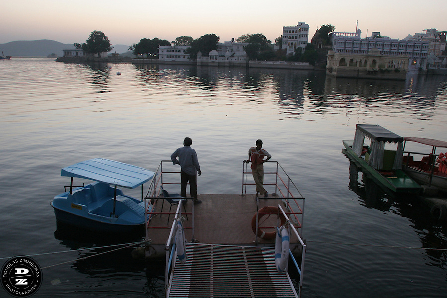 "Two paddle boat vendors watch the sunset at Lal Ghat at Pichola Lake in Udaipur, Rajasthan, India.  Udaipur is located in a valley surrounded by the Aravalli hills, and at its center is the Pichola Lake.  The scenic city has been described as ""the most romantic spot on the continent of India"" (by Colonel James Tod).  Photograph by Douglas ZImmerman"