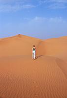 Tourist climbing up a sand dune in the Sahara Desert, Morocco