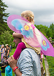 Old Westbury, New York, USA. 28th June 2015. A young girl, dressed in a fairy costume, sits on shoulders of father, as they watch dancers, on grounds of historic Old Westbury Gardens, a Long Island Gold Coast estate, during its Midsummer Night event.