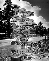 It doesn't seem to matter where the war has carried the GI.  He retains a keen sense of humor and an equally sharp yearning for home.  Signpost at a crossroads in Tacloban on Leyte reflects Joe's love of a gag and names and places he misses.  Ca.  1944-45.  (Coast Guard)<br /> Exact Date Shot Unknown<br /> NARA FILE #:  026-G-4650<br /> WAR &amp; CONFLICT BOOK #:  1213