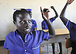 A girl raises her hand during class in a school in the Southern Sudanese village of Kenyi. The school was constructed by the United Methodist Committee on Relief (UMCOR).  Families here are rebuilding their lives after returning from refuge in Uganda in 2006 following the 2005 Comprehensive Peace Agreement between the north and south.