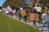 Occupy Orange County, Irvine marchers walk down the sidewalk of Alton in Irvine, CA as a part of their Saturday protest against banks.  Many signs are visible.  Taylor and Rick are visible near the front of the line.