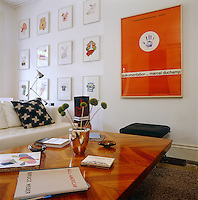 One wall in the living room displays a collection of framed artwork and a large poster