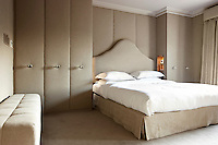 A bed with a sculpted headboard is fitted between a wall of cupboards upholstered in linen