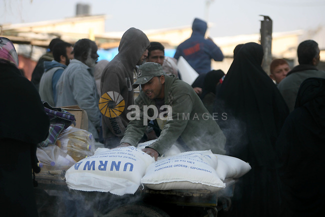 Palestinians receive their food aid from a UN distribution centre in the Rafah refugee camp, southern Gaza Strip on Jan. 03, 2013. Photo by Eyad Al Baba