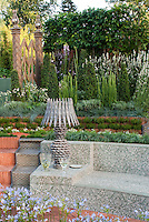 Tiled garden bench surrounds a sunken deck, with beautiful Moorish style landscaping, with garden lamp to create outdoor room feeling, Agapanthus blue flowered bulbs, ornamental grasses, etc, in several levels