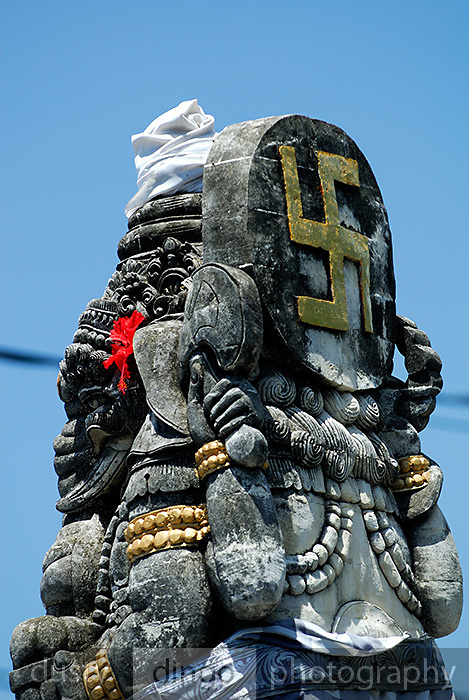 Rear view of crossroad statue of elephant god Ganesh (Ganesha, Gannesha) with ancient Hindu symbol, the swastika. Sanur, Bali, Indonesia.
