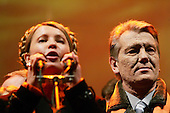 """Kiev, Ukraine.December 28, 2004..Opposition candidate Viktor Yushchenko and his political partner Yulia Timoshenko (at microphone) take center stage on Maidan Independence Square as thousands of Orange flag waving supporters rally to their side. ..Election polls show him as a clear winner however he has not yet been declared the winner nor has his opponent refuses to admit defeat...The first round of voting was considered fraudulent when the ruling president Viktor Yahukovich won and the opposition candidate Viktor Yushchenko lost. ..Several hundred thousand Ukrainians took to the streets of Kiev and held daily rallies on Maidan Independence Square. The protests lasted nearly a month before the first vote was declared invalid and a new round of elections held on December 26, 2004. ..The demonstrations would come to be known as the """"Orange Revolution"""" after the color of the opposition party."""