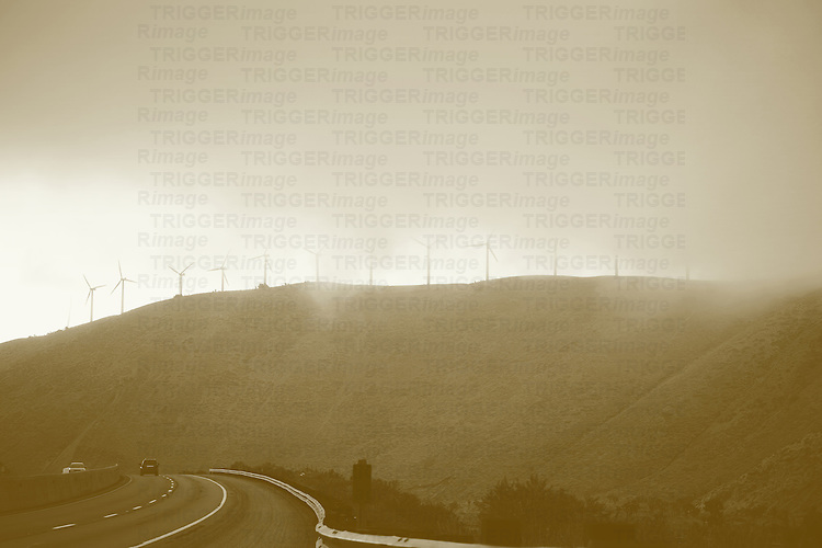 A road in the mountains with a windmill park on the mountainside in fog and with traffic.
