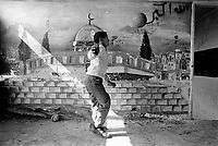State of Palestine. West Bank. Balata Camp. Palestinian refugees. A boy plays football indoors. close to a drawing from the Al-Aqsa mosque on the wall. Al-Aqsa Mosque (also known as Al-Aqsa and Bayt al-Muqaddas) is the third holiest site in Sunni Islam and is located in the Old City of Jerusalem. Graffitis on the wall. Balata Camp is a Palestinian refugee camp established in the northern West Bank in 1950, adjacent to the city of Nablus. It is the largest refugee camp in the West Bank. Balata Camp is densely populated with 30,000 residents in an area of 0.25 square kilometers. In 1991, Balata Camp was living under Isreal's occupation and rules as part as the Occuppied Territories. In the 1980s and 1990s, Balata residents played a leading role in the uprisings known as the First Intifada and the Second Intifada. Balata Camp is since 1993 under palestinian authority, located in the A zone. The Palestinian National Authority (PA or PNA) was the interim self-government body established to govern Areas A and B of the West Bank as a consequence of the 1993 Oslo Accords. Following elections in 2006, its authority had extended only in areas A and B of the West Bank. Since January 2013, the Fatah-controlled Palestinian Authority uses the name State of Palestine on official documents. The Palestinian keffiyeh is a gender-neutral chequered black and white scarf that is usually worn around the neck or head. The Palestinian keffiyeh has become a symbol of Palestinian nationalism. The Palestinian flag is based on the Flag of the Arab Revolt, and is used to represent the Palestinian people. © 1991 Didier Ruef