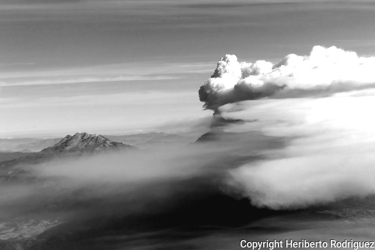 Mexican volcano Popocatepetl towers a plume of ash that covers the sky while the Iztaccihuatl appears at left back on December 19, 2000. Photo by Heriberto Rodriguez