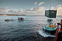 The unloading of containers from Scarlett Lucy, the ship that brings goods to Nauru only 6 times a year..The presence of the reef has prevented the establishment of a seaport, so the loading and unloading of containers is done at sea. Containers are then brought to shore with the help of an old Nauruan tug boat...Nauru, officially the Republic of Nauru is an island nation in Micronesia in the South Pacific.  Nauru was declared independent in 1968 and it is the world's smallest independent republic, covering just 21 square kilometers..Nauru is a phosphate rock island and its economy depends almost entirely on the phosphate deposits that originate from the droppings of sea birds. Following its exploitation it briefly boasted the highest per-capita income enjoyed by any sovereign state in the world during the late 1960s and early 1970s..In the 1990s, when the phosphate reserves were partly exhausted the government resorted to unusual measures. Nauru briefly became a tax haven and illegal money laundering centre. From 2001 to 2008, it accepted aid from the Australian government in exchange for housing a Nauru detention centre, with refugees from various countries including Afghanistan and Iraq..Most necessities are imported on the island..Nauru has parliamentary system of government. It had 17 changes of administration between 1989 and 2003. In December 2007, former weight lifting medallist Marcus Stephen became the President.