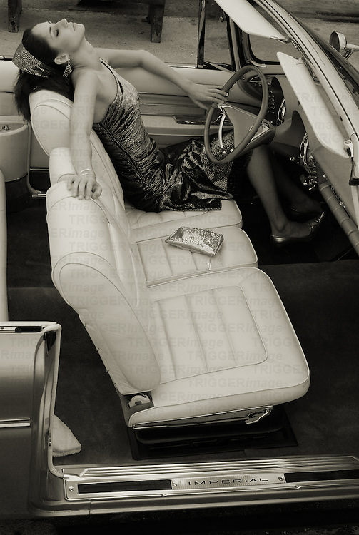 A young model sitting in the driving seat