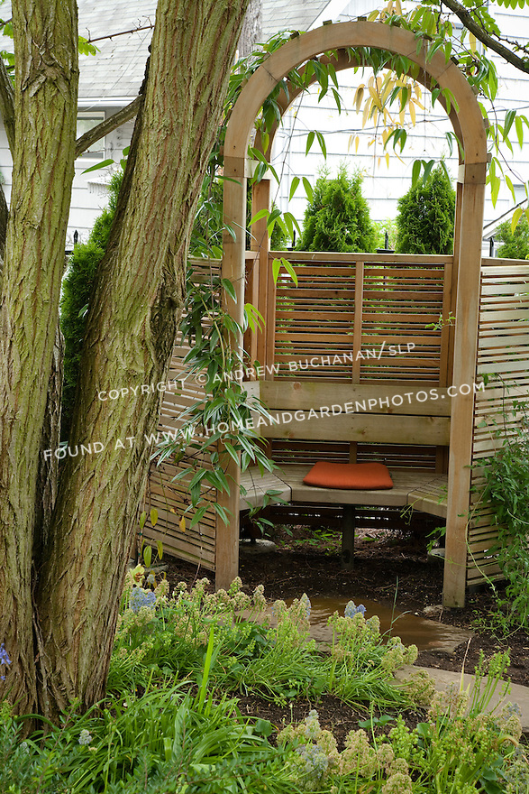 This arbor-covered bench seat provides a hidden retreat in the garden.