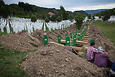 Relatives sit in front of one of the graves where 175 newly identified bodies of the 1995 Srebrenica genocide will be buried.