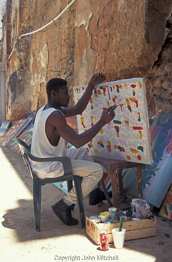 Haitian artist painting a picture on a street in old Santo Domingo, Dominican Republic.