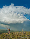 storm clouds, rainbow, spring flowers and a man holding up his arms as to direct the weather or pray, blackfeet reservation, montana