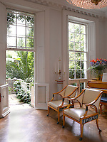 Floor-to-ceiling sash windows with small doors at the bottom lead from the living room onto the terrace and garden