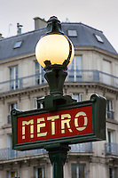 Metro sign in front of typical Parisian apartment block architecture, Paris, France