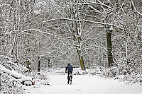 Man cycles across snow-covered Hampstead Heath, North London, United Kingdom