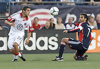 D.C. United defender Chris Korb (22) lines up an overlong pass as New England Revolution midfielder Juan Carlos Toja (7) closes. In a Major League Soccer (MLS) match, the New England Revolution (blue) tied D.C. United (white), 0-0, at Gillette Stadium on June 8, 2013.