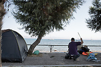 Man setting up tent in a makeshift encampment along the waterfront. Kos, Greece. Sept. 5, 2015