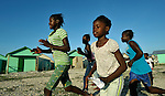 Girls run through Camp Corail, a controversial resettlement of earthquake survivors north of Port-au-Prince, Haiti. Thousands of families were relocated to Corail from flood-prone areas of the capital in 2010, yet the promises of jobs that lured them there failed to materialize.