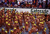 Dozens of yellow capped swimmers waiting for the start of the challenging 2.4 mile swim component of the annual Ironman triathlon on the Big Island of Hawaii.