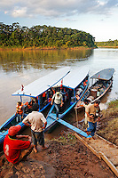 Tourists disembarking tour boat on Tambopata River, Peru